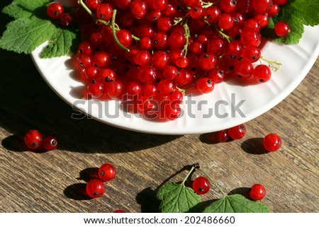 Fresh red currant in bowl on wooden background.  - stock photo