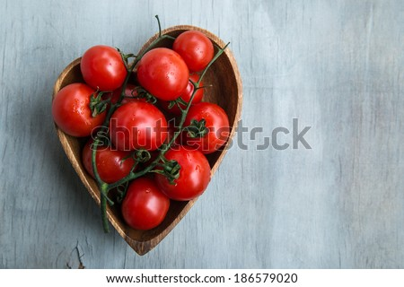 fresh red delicious tomatoes  in the heart shape wooden plate on an wooden tabletop with place for text - stock photo