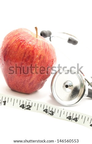 fresh red farm apple and doctor's stethoscope and tailor measuring tape on white isolated background