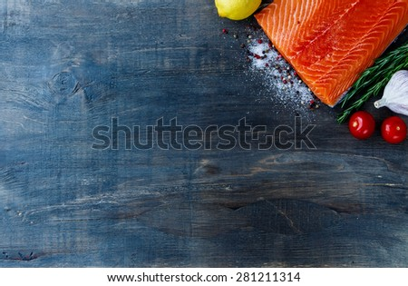 Fresh red fish fillet, aromatic spices and lemon on dark wooden table. Background with space for text. Vegetarian food, health or cooking concept. Top view. - stock photo