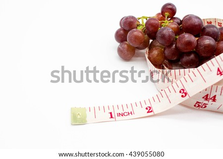 fresh red grapes fruit and tape measure isolate on white background, it mean for weight loss, diet, eat clean, healthy. Selective focus with text space - stock photo