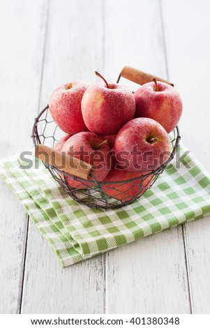 Fresh red juicy apples in a basket on a green textile on a wooden background, closeup - stock photo