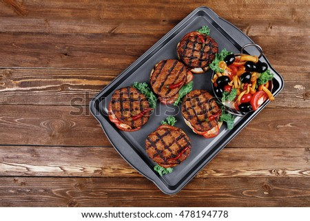 fresh red meat beef hamburger served on black tray with vegetables olives hot chili pepper tomatoes mushrooms over wooden table with empty space for text on background