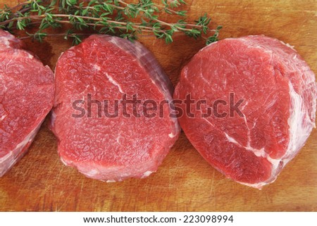 fresh red meat : three raw beef fillet chops on wooden board with thyme twig ready to prepare . isolated over white background - stock photo