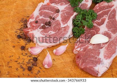 Fresh red meat with spices and parsley close-up on a wooden table.