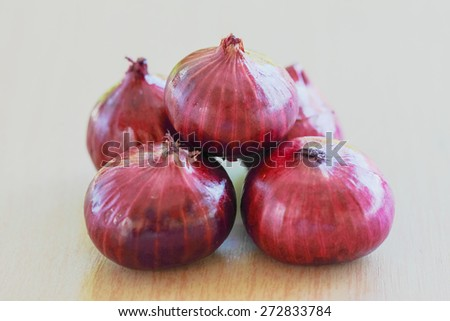 Fresh red onion with background blurring of trees in a park. The purpose of this blur effect to indicate freshness, organic and natural
