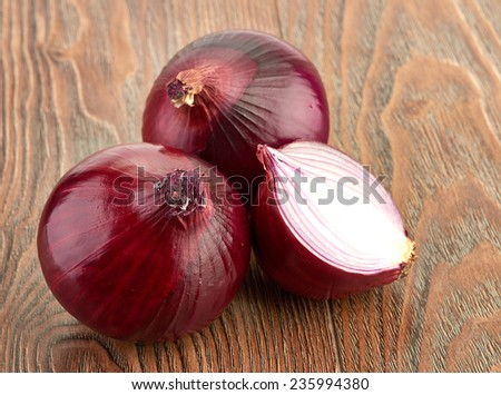 Fresh red onions on a wooden background - stock photo