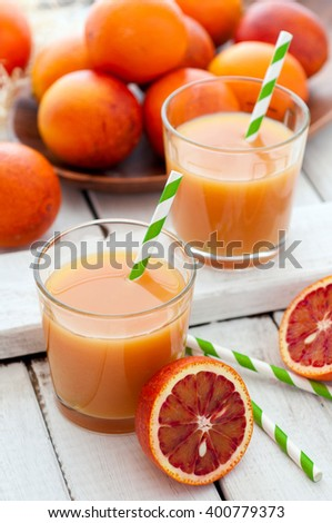 Fresh red oranges juice with fruits on white wooden background, selective focus