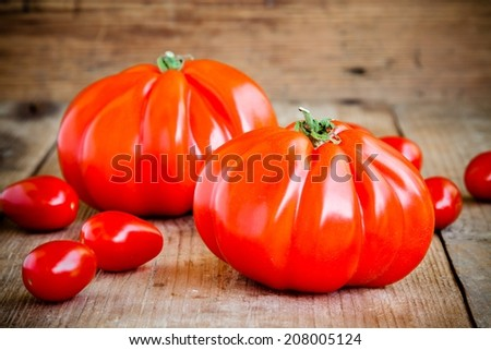 Fresh red organic heirloom and cherry tomatoes on wooden background - stock photo
