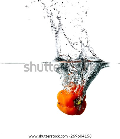Fresh red pepper drops into a water, isolated on white background