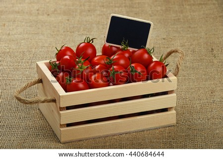 Fresh red ripe cherry tomatoes in small wooden box with black chalkboard price sign tag over jute burlap canvas background, high angle view