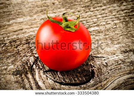 Fresh, red, ripe tomatoes on old grey wood background. Toned.