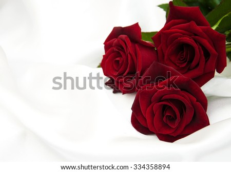 Fresh red  roses on a white silk background
