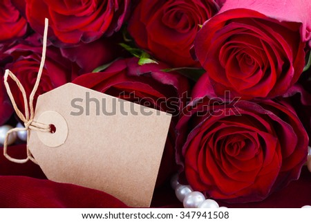 fresh red roses on scarlet velvet background with empty paper note