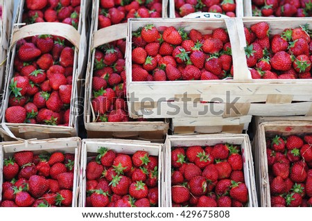 Fresh red strawberries arranged in baskets ready for sale at marketplace, background from freshly harvested strawberries - stock photo