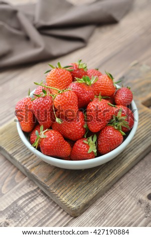 Fresh red strawberries in a ceramic bowl on wooden background - stock photo