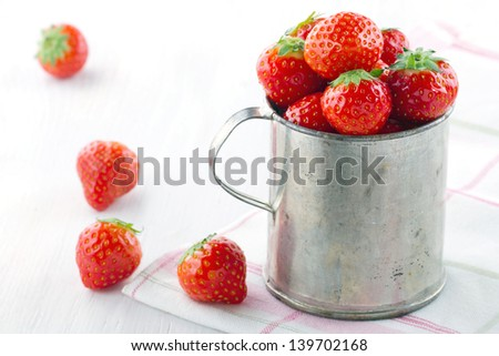 Fresh red strawberries in an old metal measurement cup on a pink striped retro towel and vintage white wooden background - stock photo