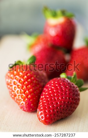 Fresh red strawberries on a wooden board.