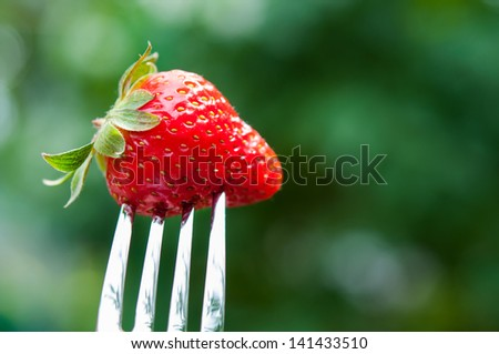 Fresh red strawberry on metal fork background - stock photo