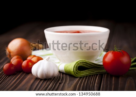 Fresh red tomato cream soup in white bowl. Dish and ingredients photography taken on old wooden table.