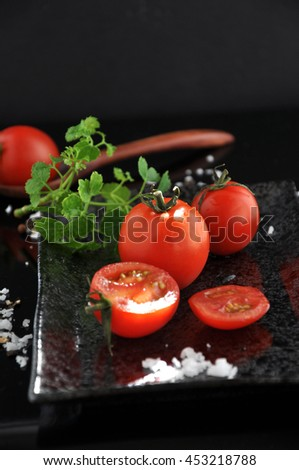 Fresh red tomato on tray with sea salt on black background - stock photo