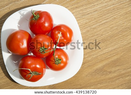 Fresh red tomatoes in white plate on wooden table - stock photo