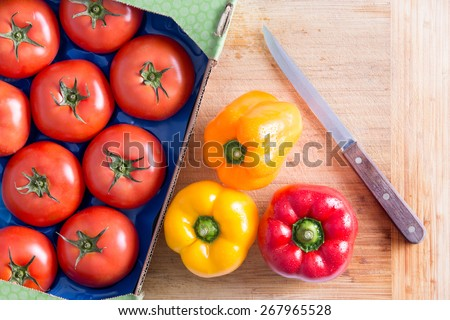 Fresh Red Tomatoes Tomatoes and Bell Peppers in Yellow and Red on Top of Wooden Chopping Board with Kitchen Knife. - stock photo