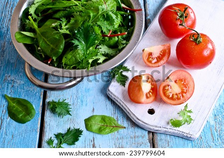 Fresh red tomatoes whole and in the context of the old painted wood surface against the green salad leaves and a metal colander - stock photo