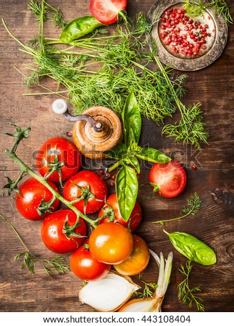 Fresh red tomatoes with green seasoning for tasty sauce cooking. Vegetarian cooking ingredients on rustic wooden background, top view - stock photo