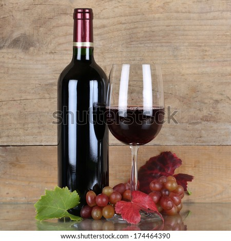 Fresh red wine in wine bottle and glass in front of a wooden background