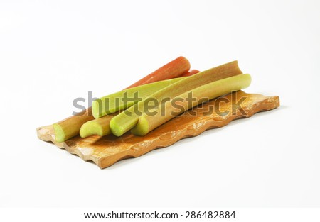 fresh rhubarb stems on wooden cutting board