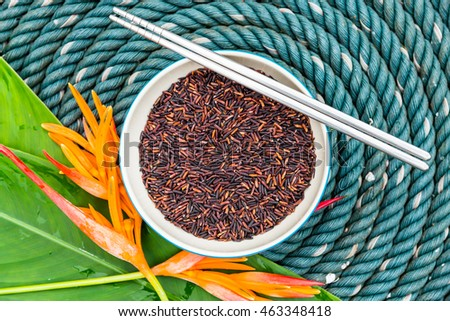 Fresh riceburry in bowl with chopsticks and orange flower on big rope