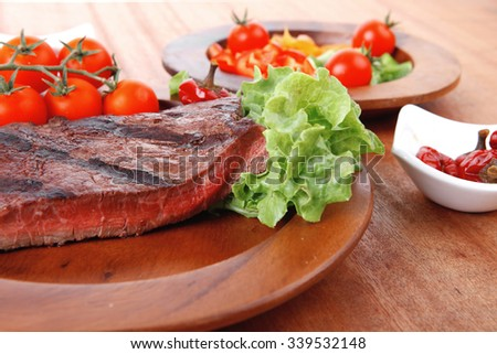fresh rich juicy grilled beef meat steak fillet with marks on wooden plate over table decorated with lettuce salad and cutlery, new york styled cuisine - stock photo