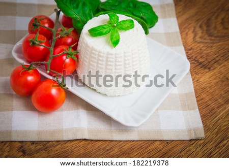 Fresh ricotta cheese with basil and cherry tomatoes on table - stock photo
