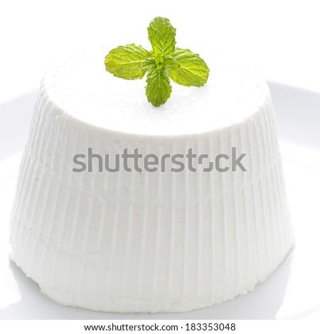 Fresh ricotta with basil leaf on white background - stock photo