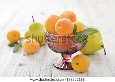 Fresh ripe apricots in glass ramekin and pear on wooden background - stock photo