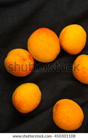fresh ripe apricots in red plate on black background, closeup - stock photo