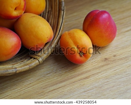 Fresh ripe apricots in wooden basket on a wooden backgroud.  Close up of apricot summer fruit. - stock photo
