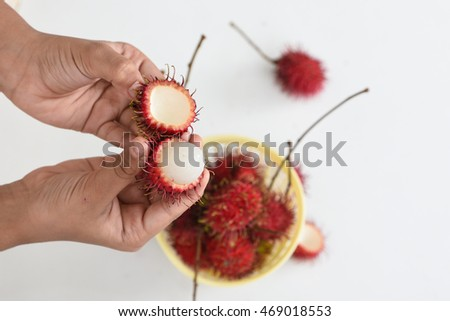 Fresh ripe asian/malasian/thai red rambutan fruit cut and peel the skin off into half with female/women's/ childs hands, Kerala India.
