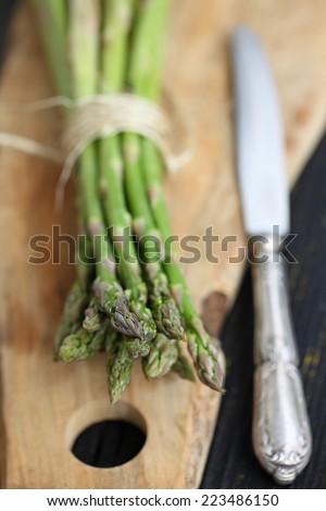 Fresh ripe asparagus in wicker basket on wooden black board. Food style Fresh ripe asparagus in wicker basket on wooden black board. Food style - stock photo