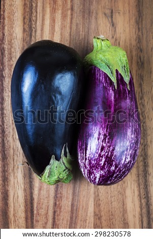 Fresh ripe aubergine and stripped raw eggplants over wood background - stock photo