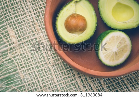 fresh ripe avocados and lime in bowl. - stock photo