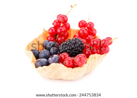 Fresh ripe berries in tartlet isolated on white background. - stock photo