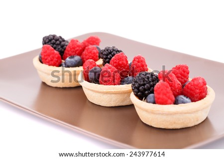 Fresh ripe berries in tartlets on brown plate. - stock photo