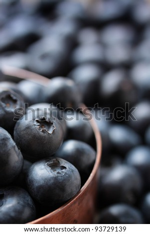 Fresh, ripe blueberries in a copper measuring cup.