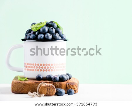 Fresh ripe blueberries in country style enamel mug on rustic wooden board over mint pastel background, selective focus