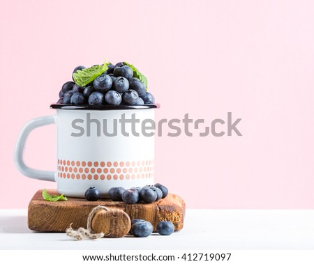 Fresh ripe blueberries in country style enamel mug on rustic wooden board over pastel pink background, selective focus