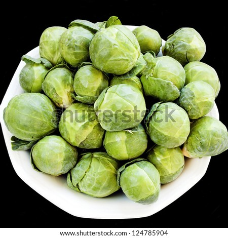 Fresh ripe brussels cabbage over black background - stock photo