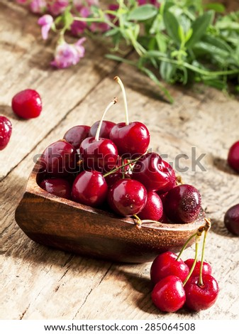 Fresh ripe cherries in a wooden bowl in the shape of a heart on an old table, selective focus