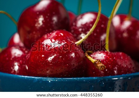 Fresh ripe Cherries on wooden table with water drops blue background